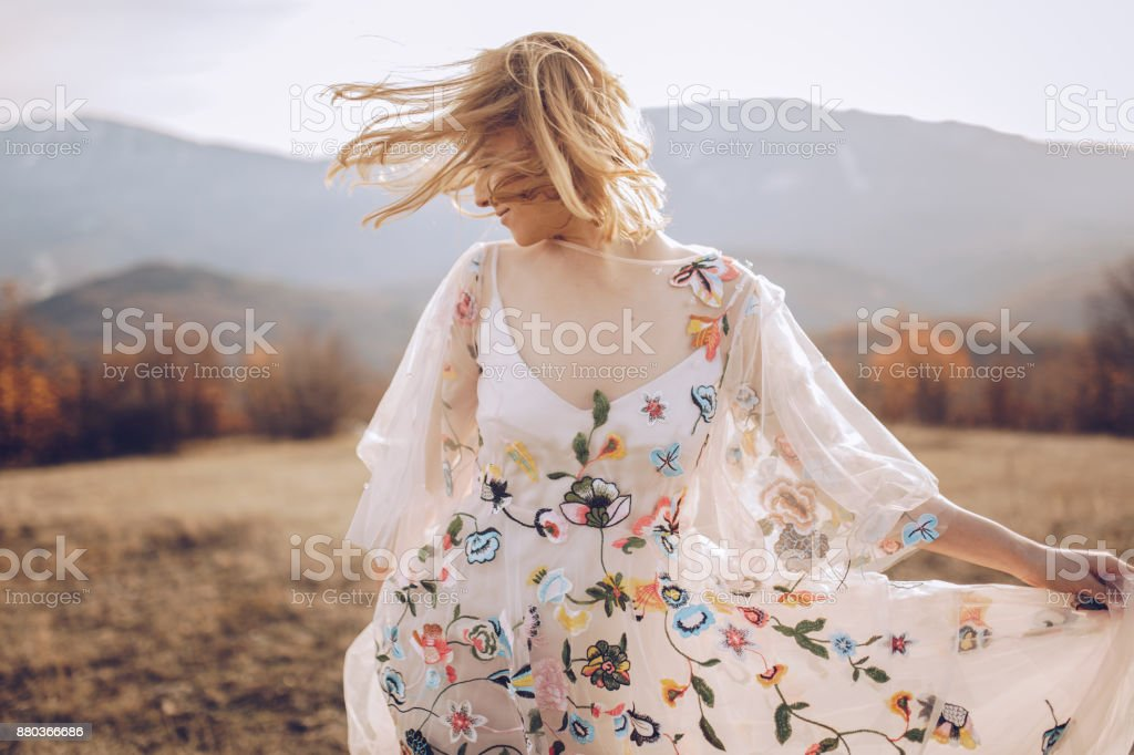 Beautiful hippie woman dancing in a meadow stock photo