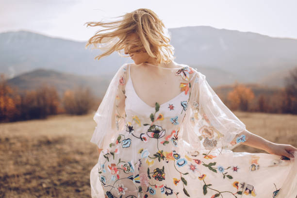 beautiful hippie woman dancing in a meadow - country fashion stock photos and pictures