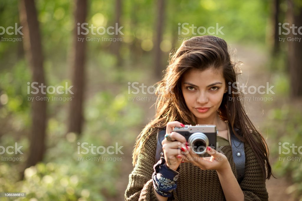 Beautiful hipster girl taking photos in the forest Outdoor shot of young woman standing in the woodland, holding camera in hands and looking at camera. Adolescence Stock Photo