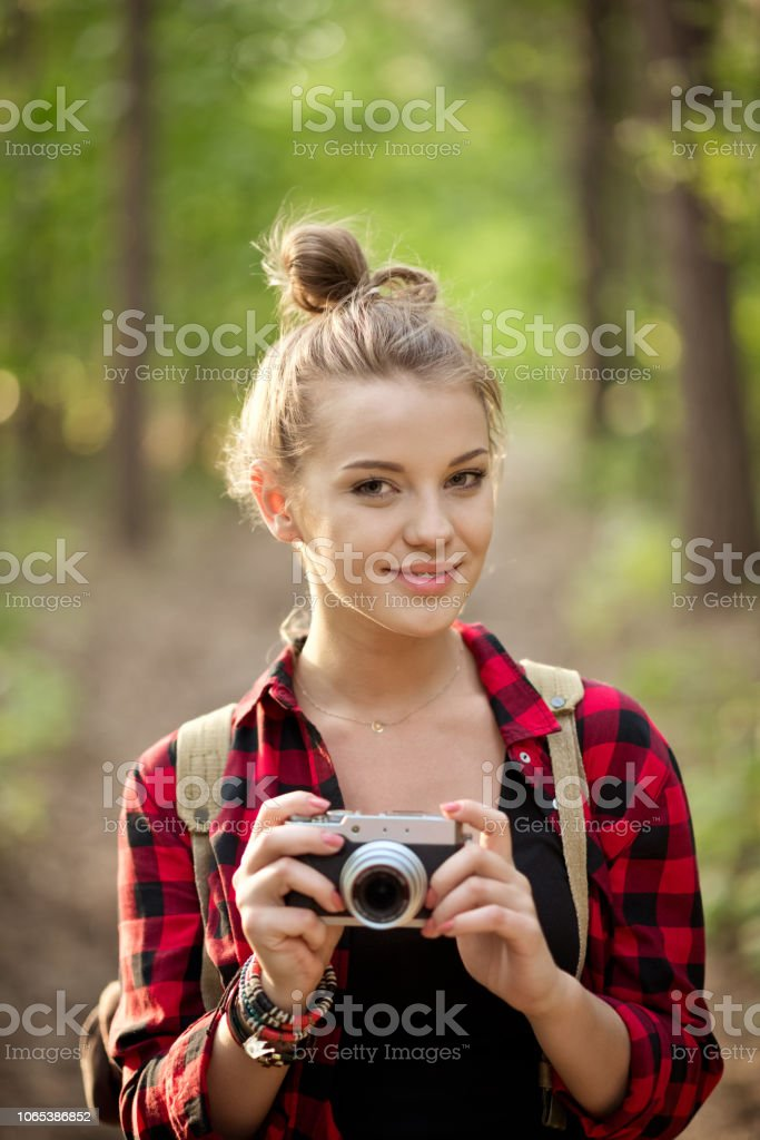 Beautiful hipster girl taking photos in the forest Outdoor shot of young woman standing in the woodland, holding camera in hands and smiling. Adolescence Stock Photo