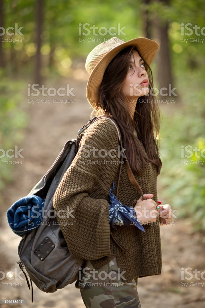 Beautiful hipster girl walking in the forest Outdoor shot of young woman hiking in the woodland, holding backpack. Adolescence Stock Photo