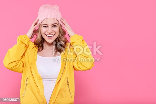 538883870istockphoto Beautiful hipster teenage girl in bright yellow jacket and pink beanie hat super excited. Attractive cool young woman fashion portrait over pastel pink background. 960938072