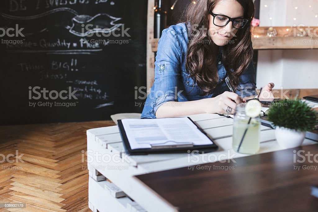 Beautiful hipster woman taking notes at modern office stock photo