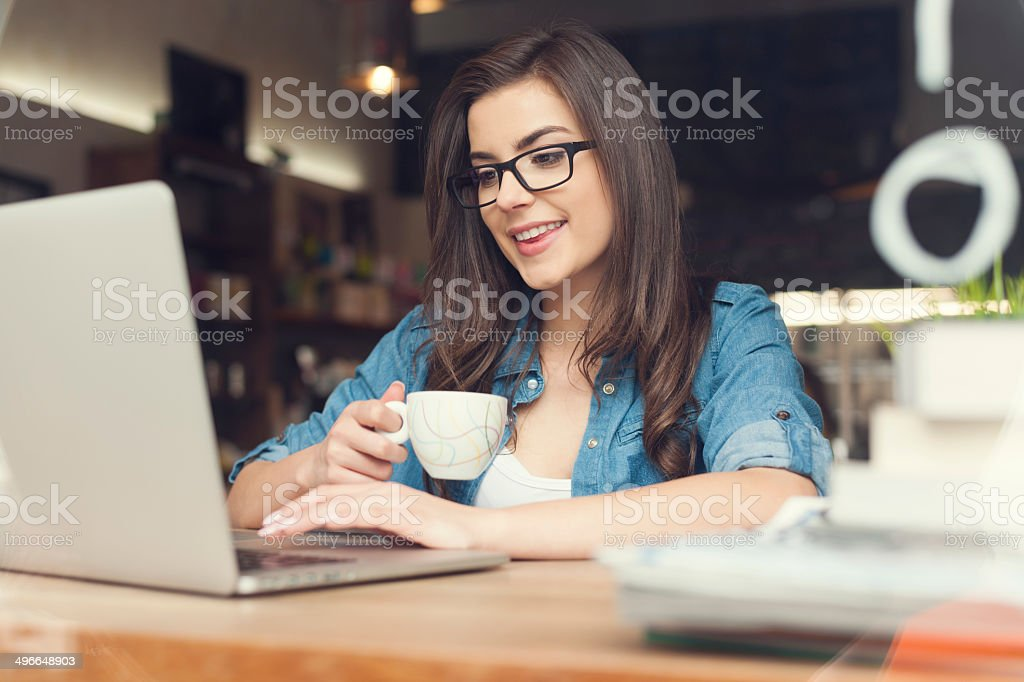 Beautiful hipster woman using laptop at cafe stock photo