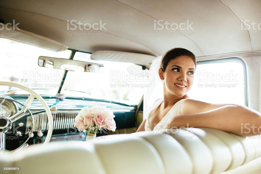 Beautiful Hispanic bride looking back in a classic car stock photo