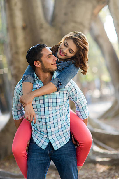 Beautiful Hispanic couple having fun outside A beautiful Hispanic couple having fun outside and looking at each other in this vertical shot. cute teen couple stock pictures, royalty-free photos & images