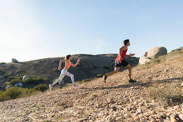 beautiful hispanic couple running uphill - jogging hill bildbanksfoton och bilder
