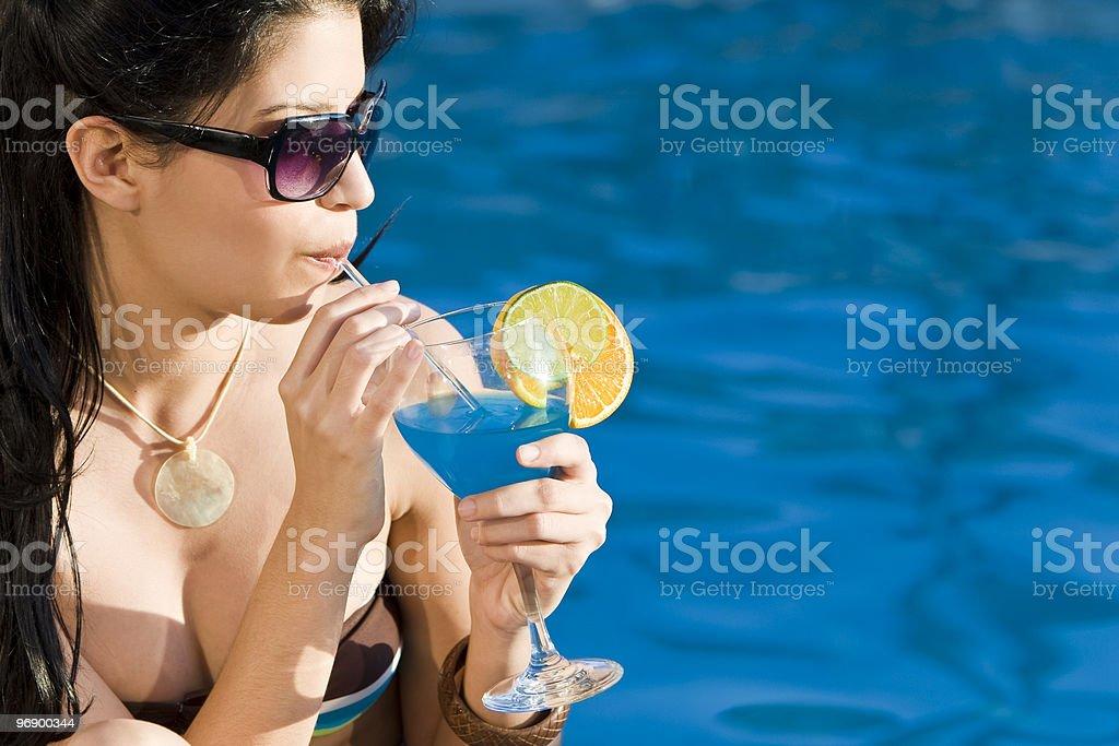 Beautiful Hispanic Latina Woman Drinking Cocktail By A Swimming Pool royalty-free stock photo