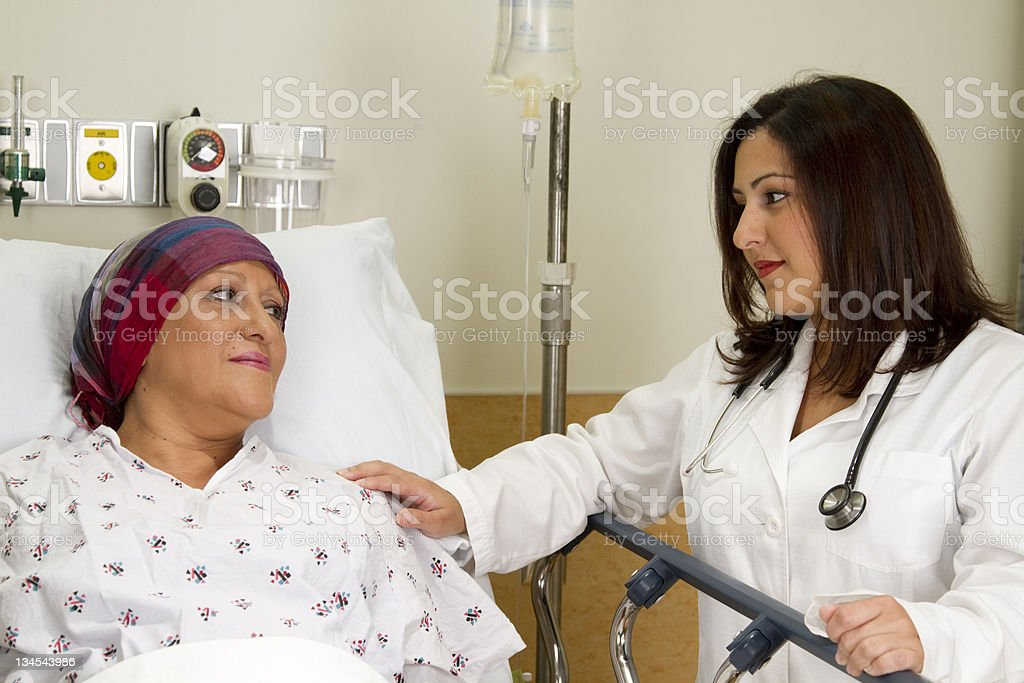 Beautiful Hispanic Medical Professional Consoling a Patient stock photo