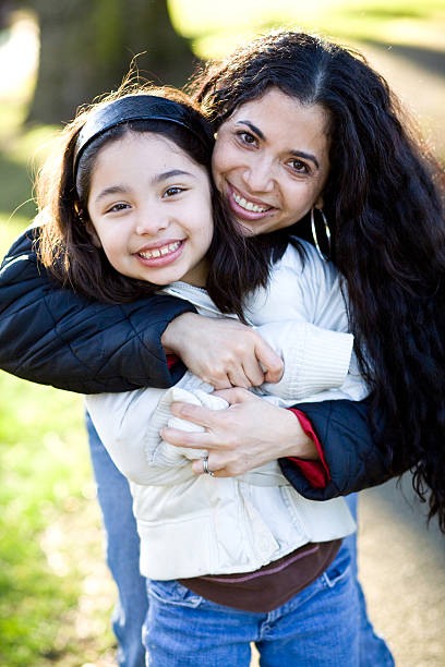 beautiful hispanic mother and daughter hugging in a park stock photo
