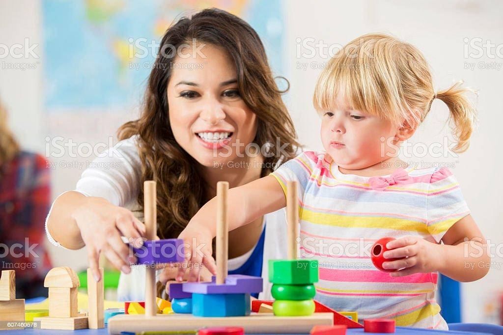 Beautiful Hispanic teacher works with cute blonde preschooler stock photo