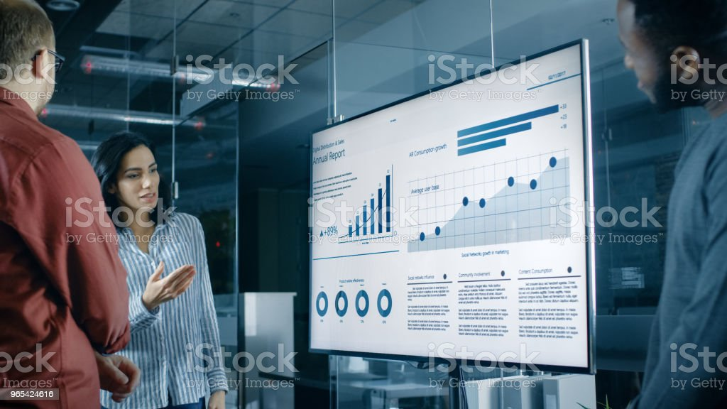 Beautiful Hispanic Woman Analyzes Statistics, Charts and Pies with Company's Growth Shown on a Wall TV. stock photo