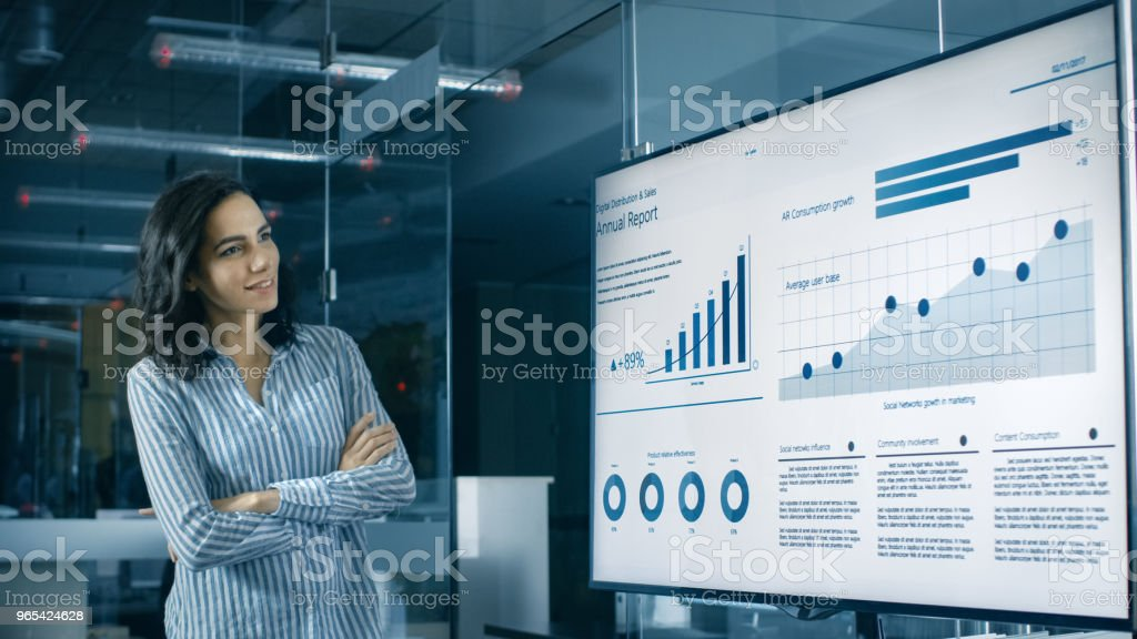 Beautiful Hispanic Woman Analyzes Statistics, Charts and Pies with Company's Growth Shown on a Wall TV. royalty-free stock photo