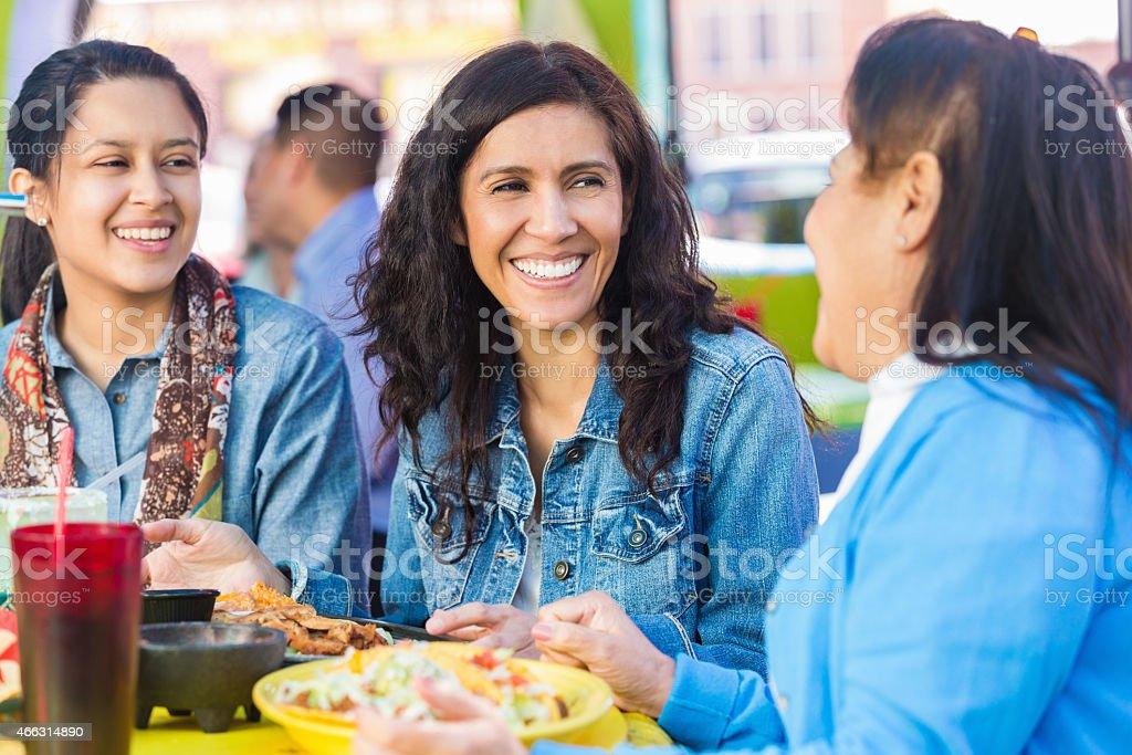 Beautiful Hispanic woman having lunch at restaurant with family stock photo