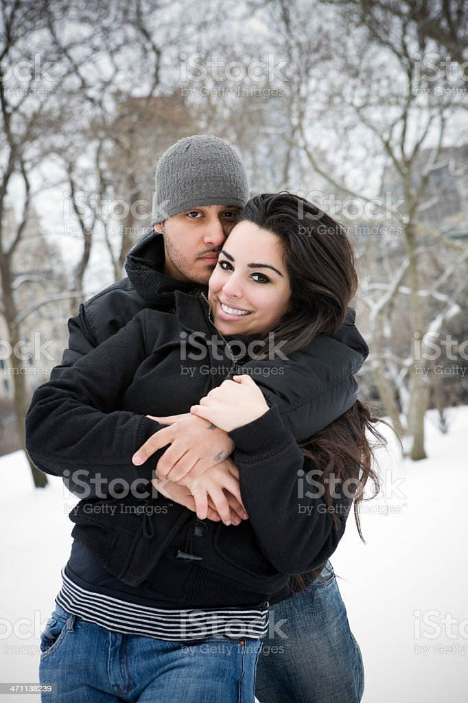 Beautiful Hispanic Young Couple Embracing in Snow, at Camera royalty-free stock photo