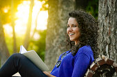Beautiful Hispanic young woman reading a book on a bench in the park