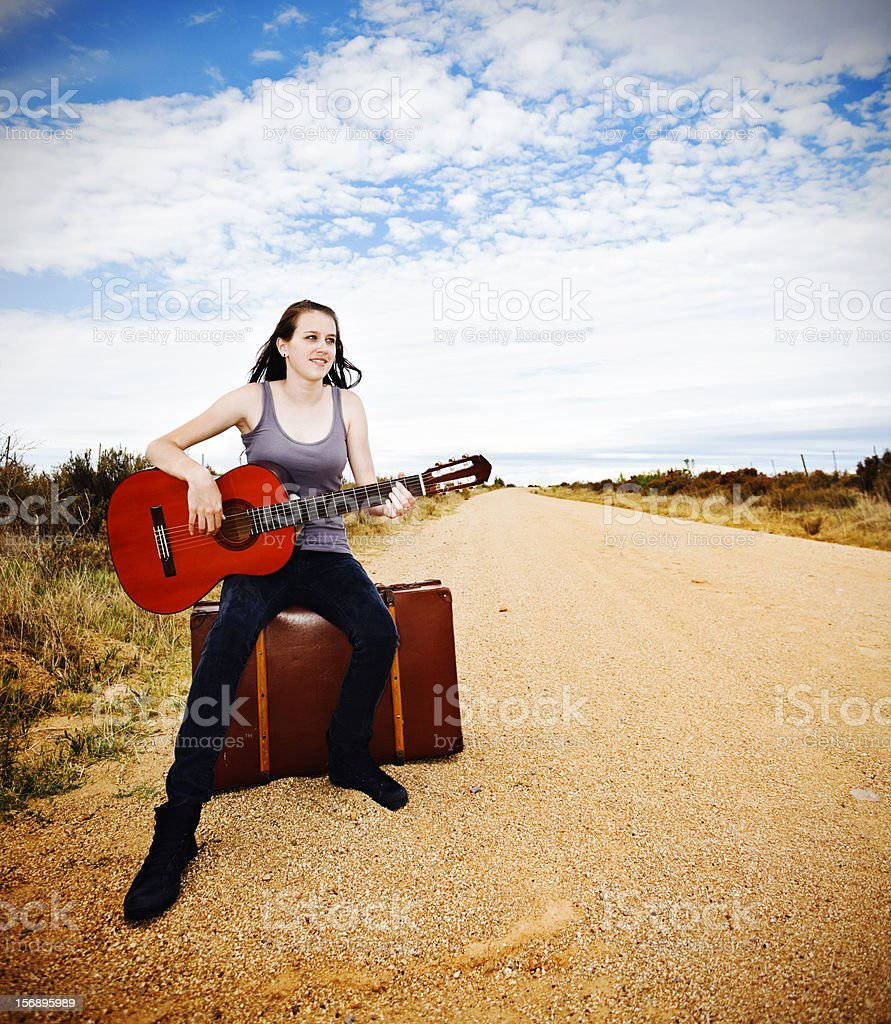 Beautiful hitchhiker with guitar waits for a ride to fame stock photo