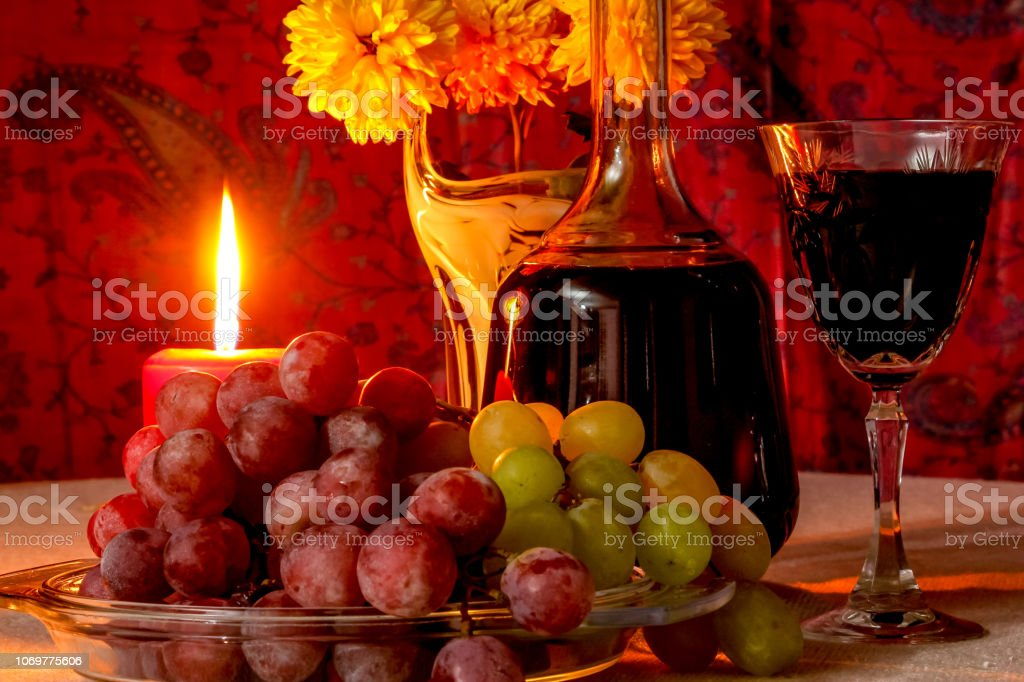 White and black grape, bottle and glass of wine, flowers, on table...