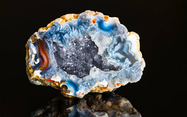 Beautiful hollow agate semi precious stone with clear raw crystals inside geode. Mineralogy stock photo
