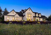 Beautiful Luxury Home Exterior at Night with Sunset Reflection in Windows and Deep Blue Sky. Small colorful flowers make up foreground
