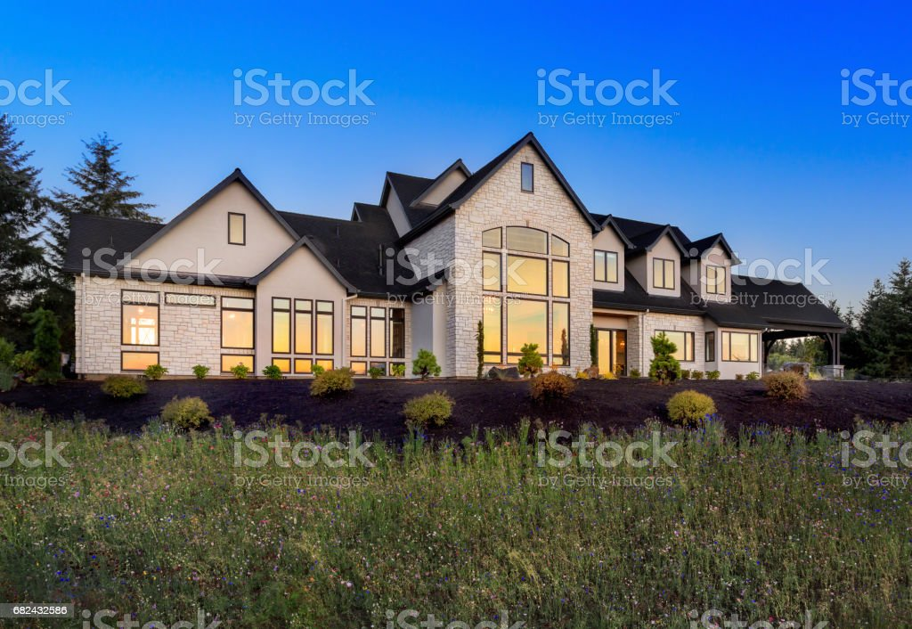 Beautiful Home Exterior at Night: Large Expansive and Stately Home stock photo