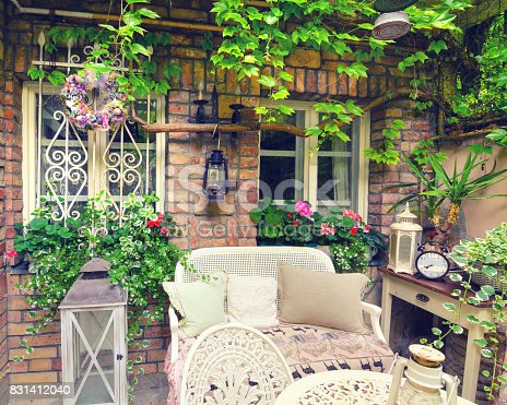 Beautiful home garden and yard in vintage style decorated with plants, flowers, old furniture and antique lamps.