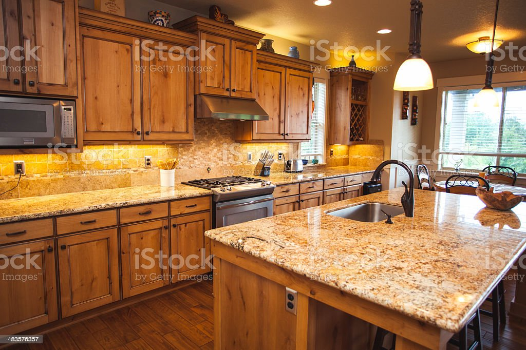 A clean spacious modern home kitchen with beautiful wood cabinets and...