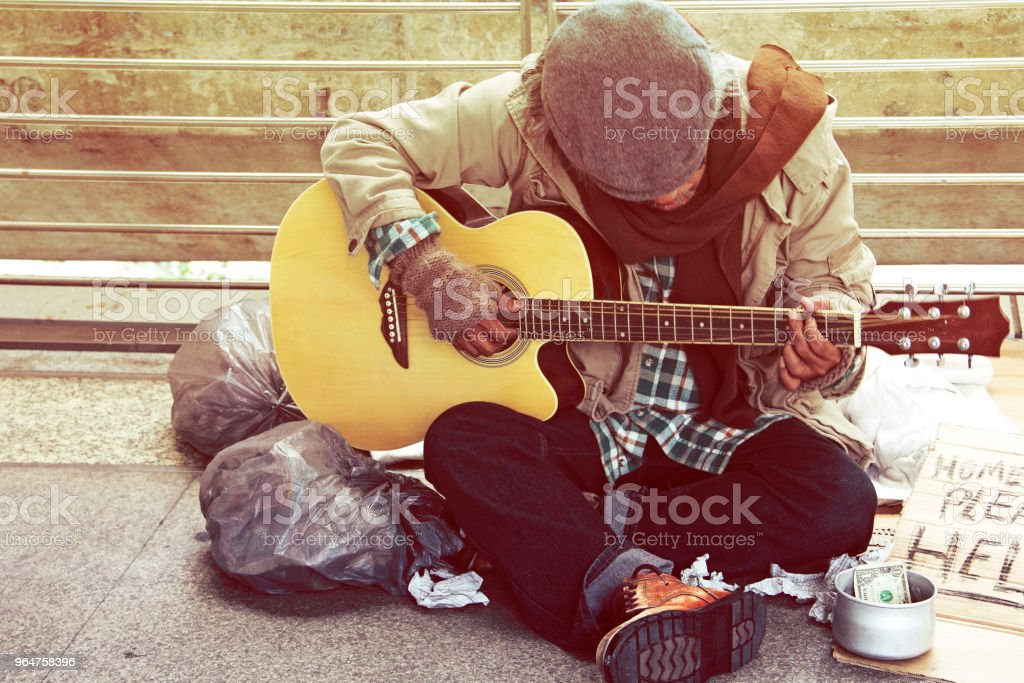 Beautiful Homeless man playing guitar on walking street in the capital city. royalty-free stock photo