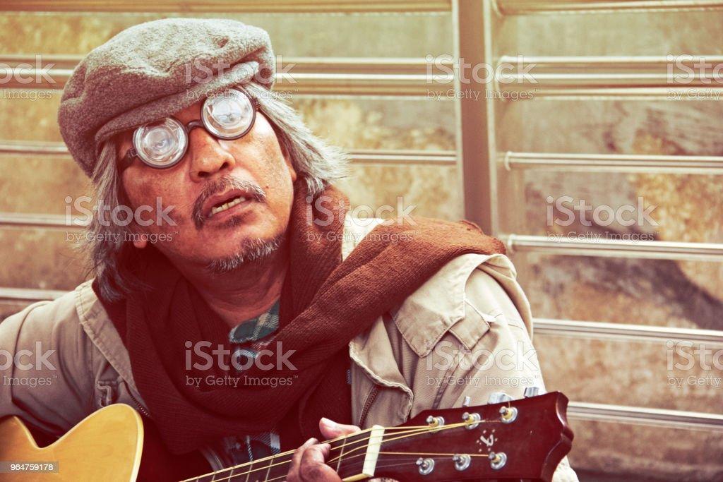 Beautiful Homeless man portrait playing guitar on street royalty-free stock photo