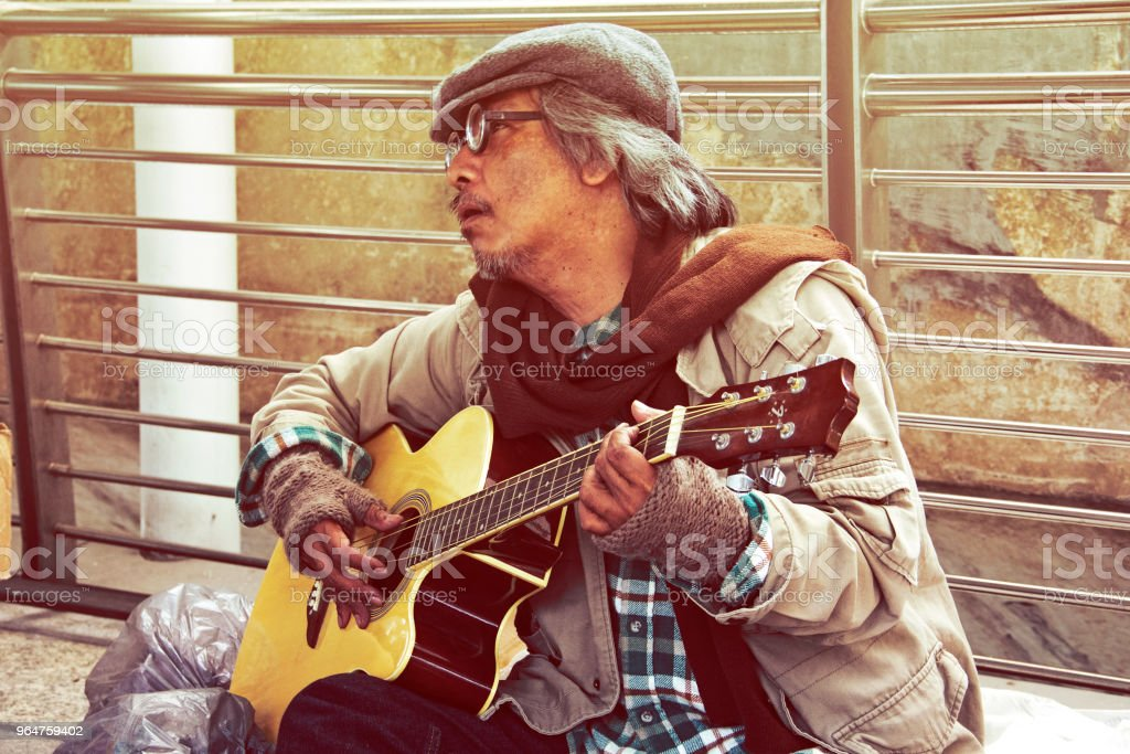 Beautiful Homeless man portrait playing guitar on street. royalty-free stock photo