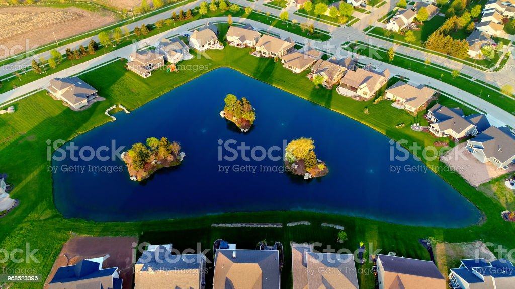 Beautiful homes around pond with islands. stock photo