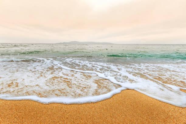 schöner horizont landschaft mit weichen welle der türkisfarbenen meer am sandstrand im vordergrund. dramatische sonnenaufgang himmel im hintergrund. - roll tide stock-fotos und bilder