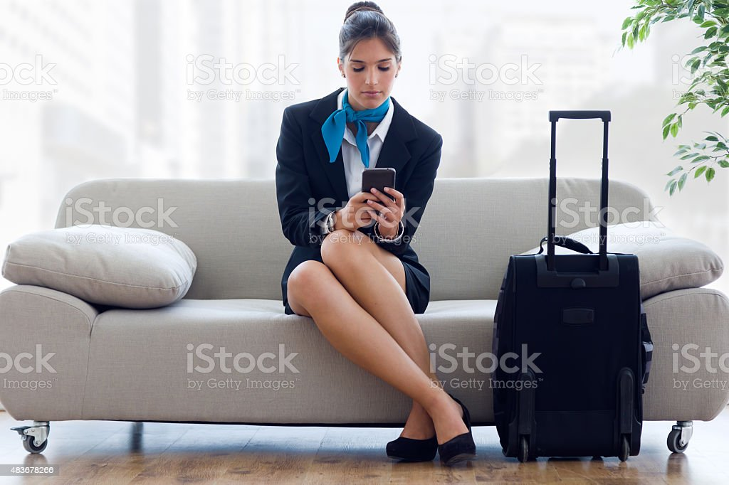 Beautiful hostess in airport with mobile phone. stock photo