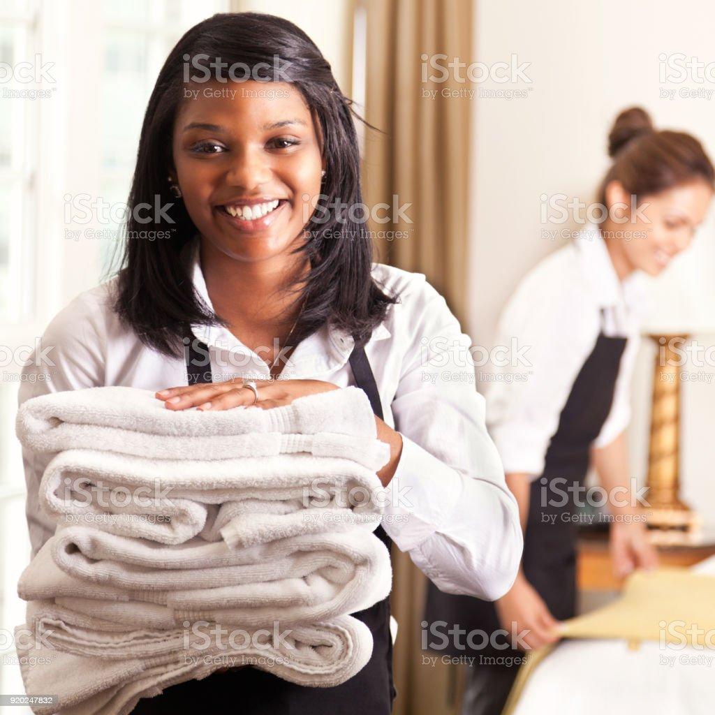 Schöne Zimmermädchen halten Stapel Handtücher – Foto