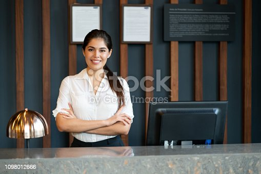 Beautiful hotel manager stading behind check in counter smiling at camera with arms crossed - Business industry concepts