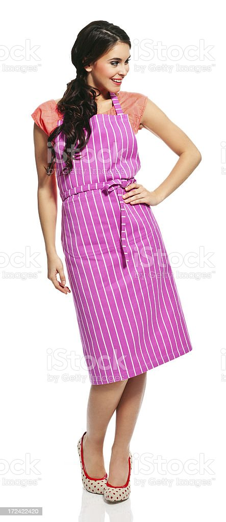 Beautiful housewife Full lenght portrait of beautiful young woman wearing an apron, standing against white background and looking away. 20-24 Years Stock Photo