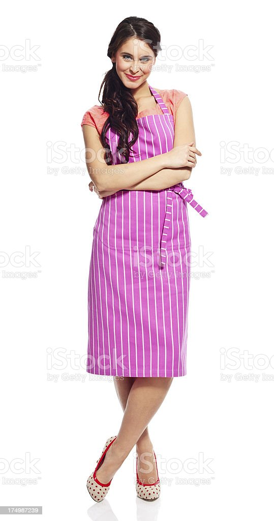 Beautiful housewife Full lenght portrait of confident young woman wearing apron, standing against white background with crossed arms and smiling at the camera. 20-24 Years Stock Photo