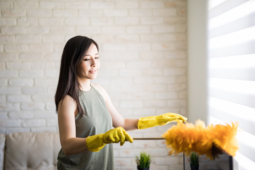 Young woman dusting television top wearing yellow gloves with orange duster