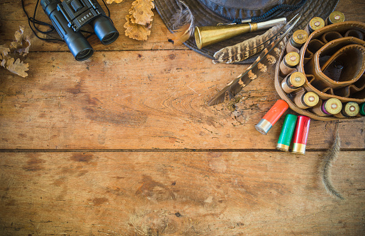 Hunting equipment on the old wooden background with copy space