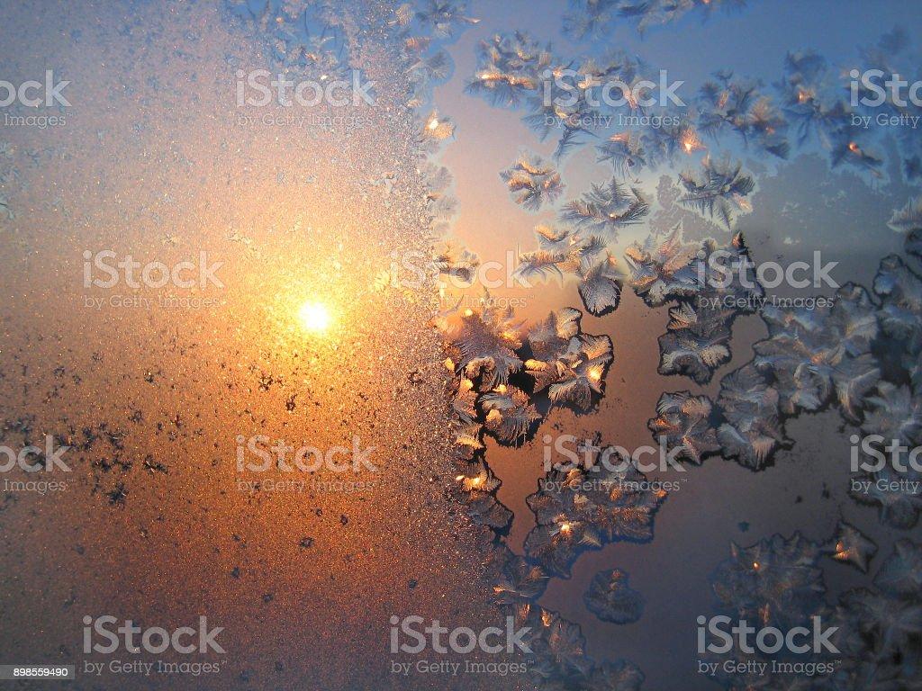 Beautiful ice pattern and sunlight on winter glass stock photo