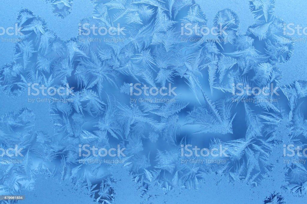 Beautiful ice patterns on a frozen winter glass stock photo