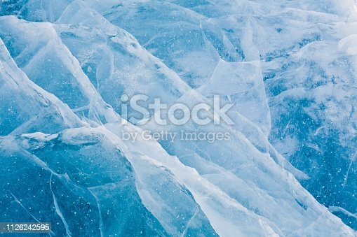 Beautiful icy snowy blue texture. The surface of a winter lake, reservoir. Frozen snow water. Ice texture design pattern