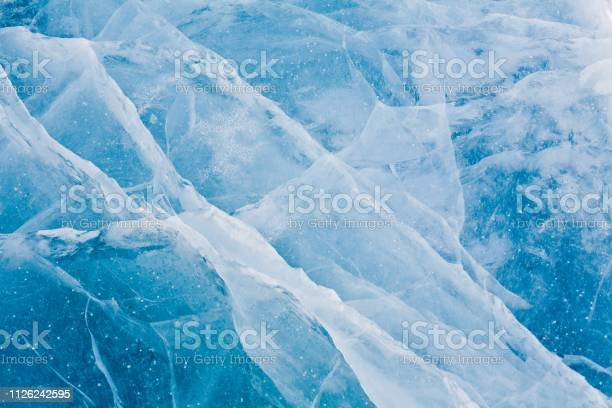 Photo of Beautiful icy snowy blue texture. The surface of a winter lake, reservoir. Frozen snow water.