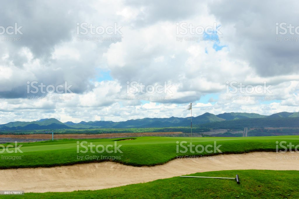 beautiful idyllic view green with sand trap and white flag and view of mountain, blue sky with clouds stock photo