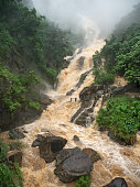Beautiful photo of fast water stream from overflooded river flowing down from the mountain slope during heavy rain