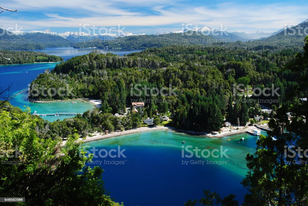 Beautiful incredible view of a blue, green and turquoise bay of a lake, surrounded by a forest and with the Andes in the horizon, Villa la Angostura, Argentina stock photo