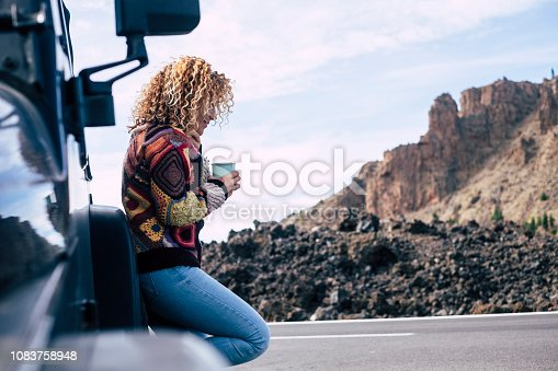 istock beautiful independent curly blonde middle age caucasian woman rest after a travel with her off road black car parked near the street. Mountains and sky in background for adventure concept and alternative vacation 1083758948