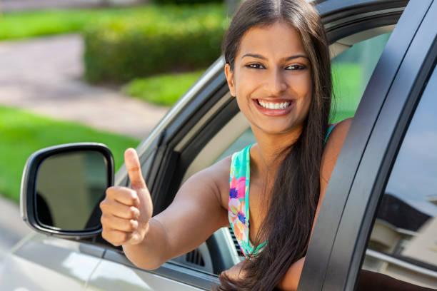 Hermosa joven asiática india o niña que se inclina hacia fuera de un coche dando un pulgar hacia arriba en el sol de verano sonriendo con dientes perfectos y el pelo largo. Concepto de alquiler de coches, alquiler o prueba de conducción. - foto de stock
