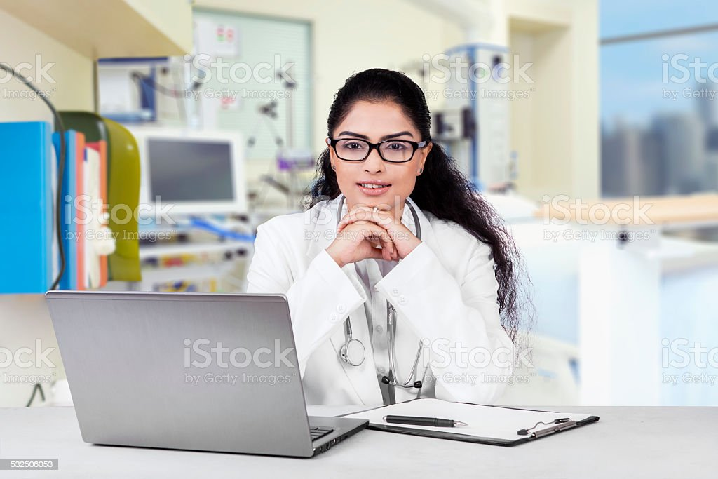 Beautiful indian doctor in the workplace stock photo