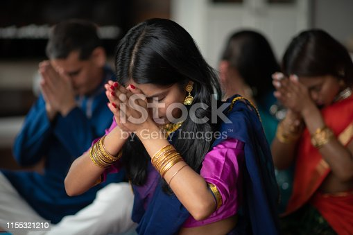 A beautiful Indian family sits in their living room one afternoon praying together. They are celebrating and giving thanks during the holiday Diwali. They are bonding as they are donned in traditional clothing.